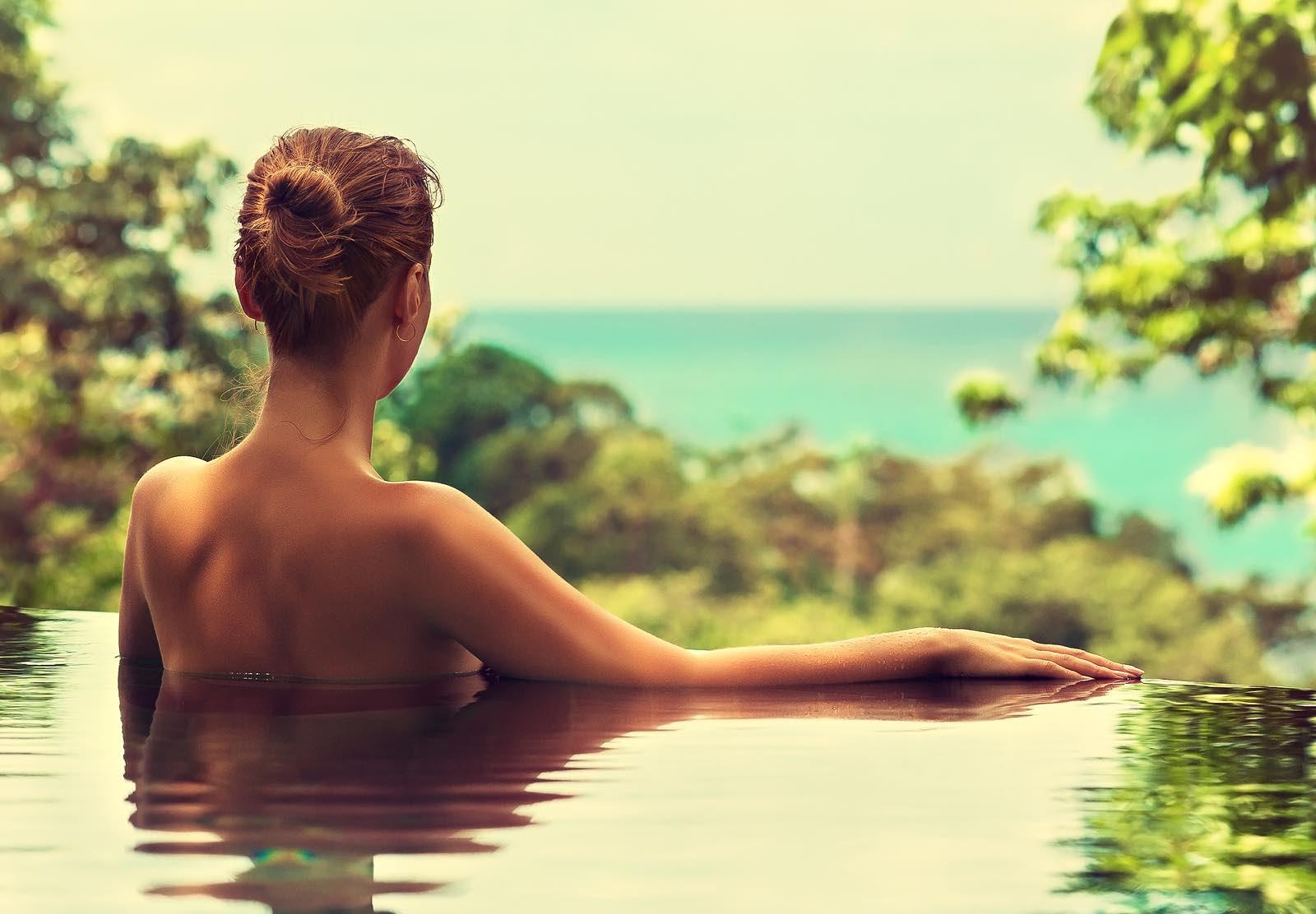 Beautiful girl rests in the swimming pool , sunbathing.