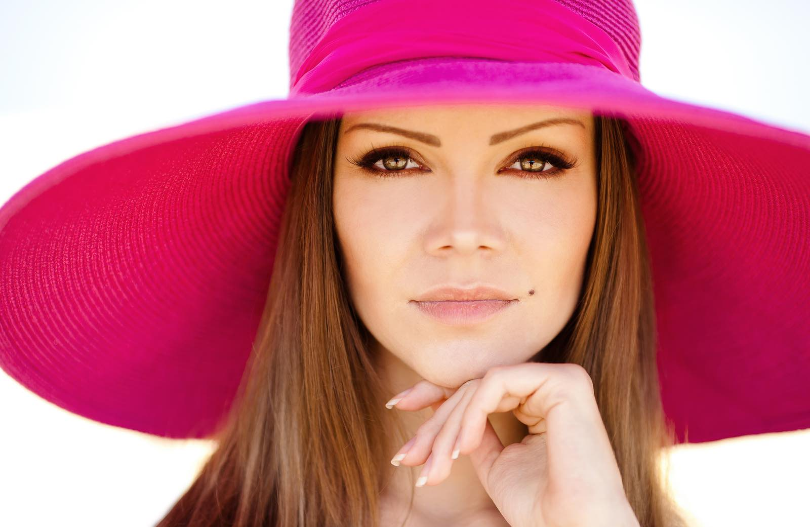 Beautiful woman in red hat with large fields.