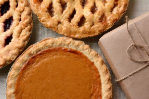 High angle closeup of three fresh baked holiday pies and a plain paper wrapped package. The traditio
